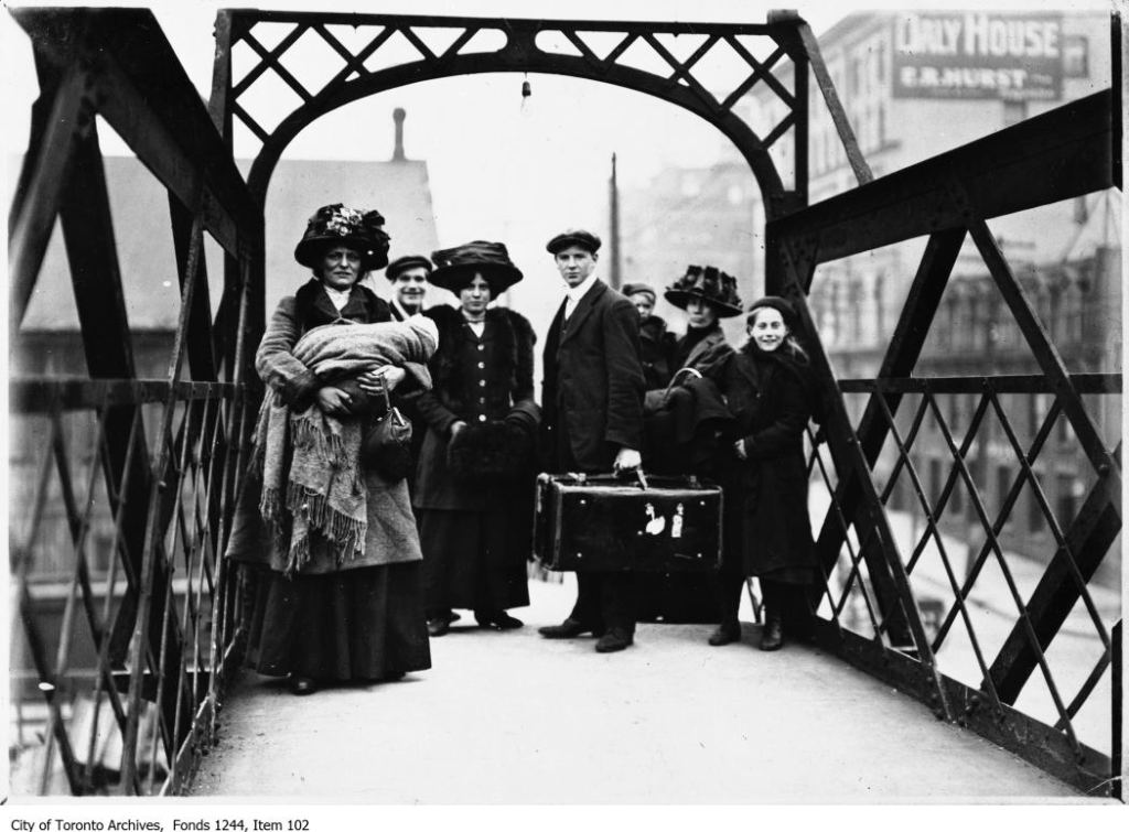 """City of Toronto Archives, Fonds 1244, Item 102. William James photographer. A British immigrant family standing on """"The Bridge of Sighs"""", the pedestrian bridge crossing the many rail lines at Toronto's Union Station."""
