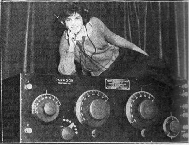 """A model, Rosalie Deneve, lying on top of a large mock-up of a radio receiver at a 1923 radio convention. Exhibit by Adams-Morgan Co.promoting their Paragon line of receivers at the 3rd Annual Convention of the 2nd Radio District, held at Hotel Pennsylvania, New York City, March 1-3, 1923. Radio broadcasting sprang up spontaneously in the US in 1920, igniting a ""radio craze"" among a Roaring 20s public fascinated by this new high-tech entertainment. The first commercial vacuum tube receivers like this one came out in 1920, made possible by a market-sharing and patent cross-licensing agreement brokered in 1919 by the US government between corporate giants Westinghouse, General Electric, AT&T, United Fruit, and RCA. Tuned radio frequency (TRF) receivers like this had multiple tuned circuits (two big knobs, center) which had to be tuned in tandem to bring in a station."" Caption:""Rosalie Deneve, of New York, listening in on the huge Paragon set at the Second Annual Convention. Date3 March 1923 Source Retrieved January 28, 2014 from Radio World, Hennessey Radio Publications Corp., New York, Vol. 2, No. 25, March 17, 1923, p. 16 on Google Books"