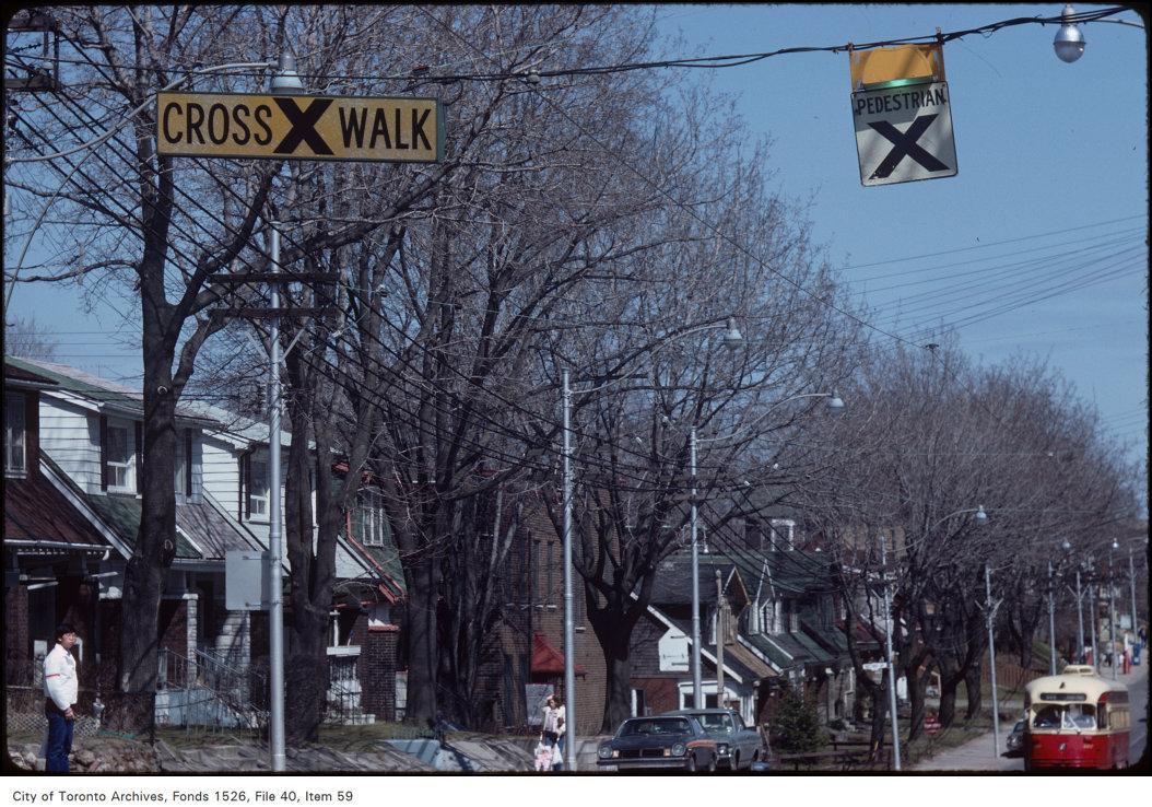 Crosswalk overhead signs located on Gerrard at Leslie, looking east