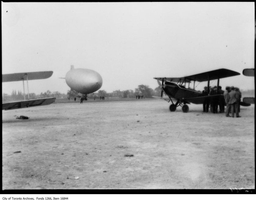 Hamilton airport, 2 planes and blimp on ground. - June 6, 1929