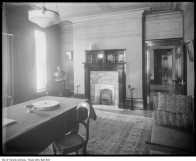 Interior of residence, showing dining room with gas lighting fixtures and radiant gas fire ca. 1916