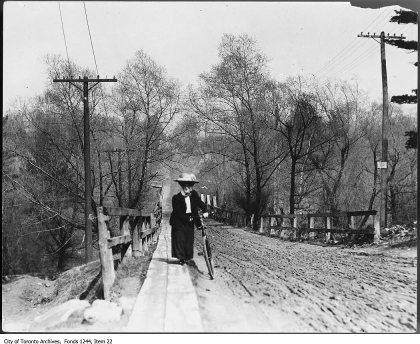 Female cyclist wheeling bicycle up muddy hill on St. Clair Avenue West. - 1907